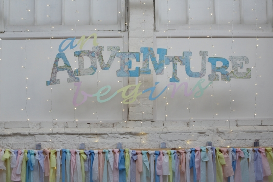 """An Adventure Begins"" map themed wedding backdrop"